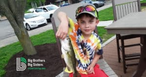Boy holding fish he caught